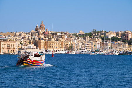old houses: Birgu, MALTA - JULY 24, 2015:  The view of historical buildings of Birgu across the Dockyard creek  with the Captain Morgan Cruises ship going to the coast, Malta.