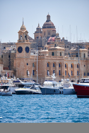 dockyard: Birgu, MALTA - JULY 23, 2015: The yachts moored in the harbor in Dockyard creek with the view of clock tower of Malta Maritime Museum and the dome of St. Lawrences Church on the background. Malta. Editorial