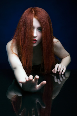 frightening: Beautiful frightening young woman with ginger hair  over reflection mirror on blue background