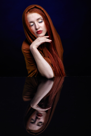 ginger hair: Beautiful young woman with ginger hair and closed eyes over reflection mirror on blue background