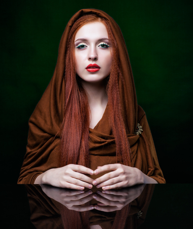 color model: Beautiful young woman with ginger hair and scarf on green background