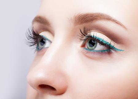 Close-up shot van vrouwelijk gezicht make-up met pistache kleur ogen en groene eyeliner
