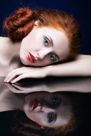 ginger hair: Beautiful young woman with ginger hair  over reflection mirror on blue background