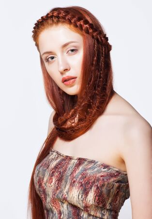 Young ginger woman with red braids hairdo on white background