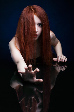 stylish hair: Beautiful frightening young woman with ginger hair  over reflection mirror on blue background