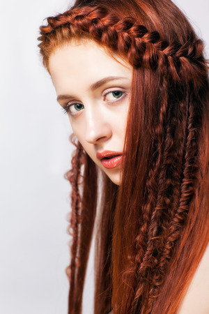 braids: Young ginger woman with red braids hairdo on white background