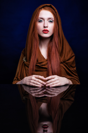 luxe: Beautiful young woman with ginger hair and scarf over reflection mirror on blue background Stock Photo