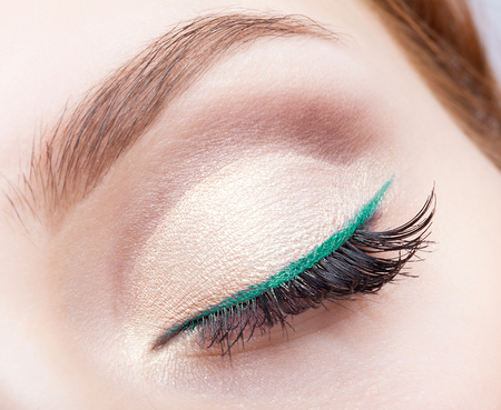 Closeup shot of female face makeup with closed eye and green eyeliner Foto de archivo