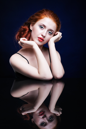 luxe: Beautiful young woman with ginger hair  over reflection mirror on blue background
