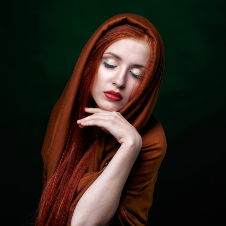 Beautiful young woman with ginger hair and closed eyes on green background