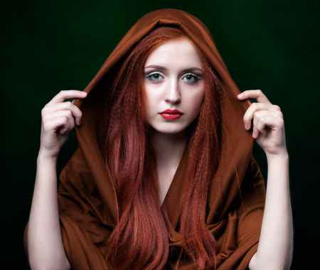 ginger hair: Beautiful young woman with ginger hair and scarf on green background