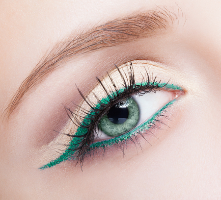 green eyes: Closeup shot of female face makeup with pistachio colour eye  and green eyeliner