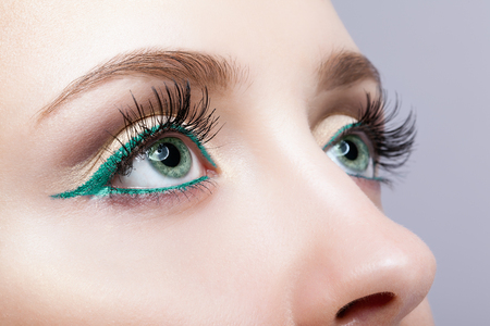 coloured: Closeup shot of female face makeup with pistachio colour eyes  and green eyeliner Stock Photo