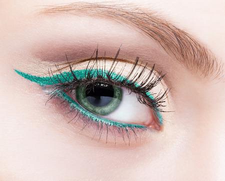 Colpo del primo piano di trucco viso femminile con gli occhi di colore verde pistacchio e eyeliner