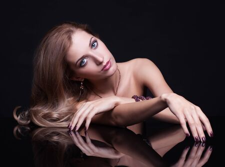 hairdo: Portrait of young beautiful woman sitting at mirror table on black background