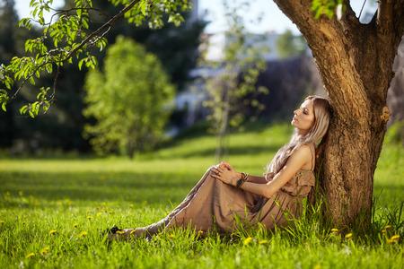 Bella giovane donna vestita in stile boho seduta sul prato verde sotto l'albero di mele nel giardino di primavera