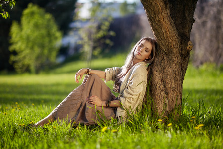 spring green: Beautiful young woman dressed in boho style sitting on green grass under apple tree in Spring garden Stock Photo