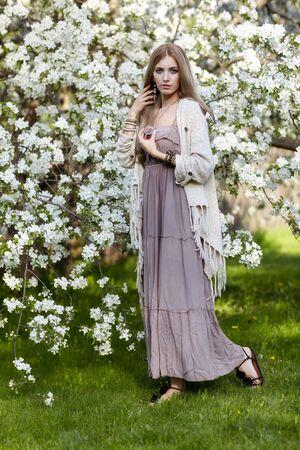 Giovane e bella donna in abito lungo stile boho su erba verde sotto melo in fiore nel giardino di primavera