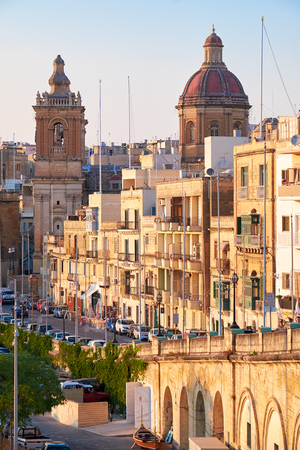 residential houses: BIRGU, MALTA - JULY 26, 2015: The view of the residential houses and St Lawrence church  dome down along the Saint Lawrence street.