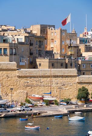 residential houses: BIRGU, MALTA - JULY 26, 2015:  view of the residential houses behind enceinte along Kalkara creek and the yachts and boats moored in the harbor.