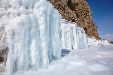 baical: Rocks covered by ice on winter siberian Baikail lake under blue sky backgroun Stock Photo