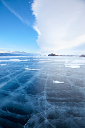 lake front: Winter ice landscape on Siberian lake Baikal with dramatic weather clouds front before the Storm