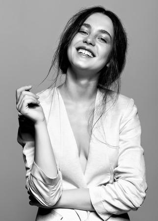 Ritratto di felice sorridente ritratto di giovane donna bruna in bianco giacca moda femminile su sfondo grigio