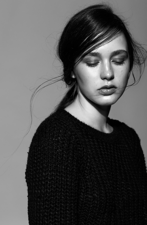 dishevelled: Portrait of beauty young brunette woman portrait in black fashion female pullover on gray background
