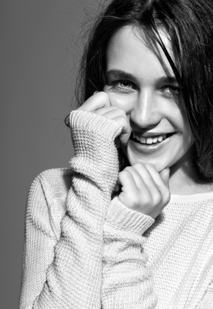 contrasty: Portrait of smiling happy young brunette woman portrait in white fashion female pullover on gray background