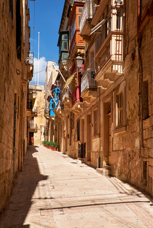 A view of the typical small street (Saint Dominic) with traditional maltese balconies on Birgu, Malta