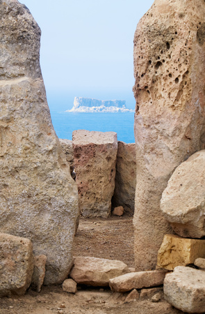 orthostat: The view of Filfla islet through the foramen of two Orthostats of megalithic temple of Hagar Qim, Malta