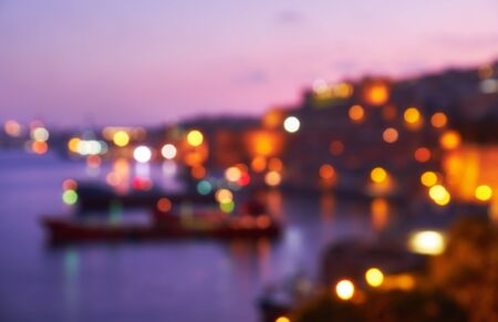 night background: The beautiful blurred bokeh night view of Grand Harbour with the cargo ships moored near St. Barbara Bastion from the Lower Barrakka Gardens, Valletta. Stock Photo