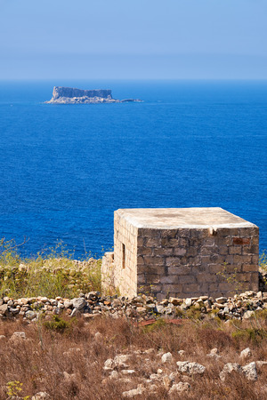 scorched: The view of Filfla islet with the guard building midst the the scorched coast of Qrendi on the  foreground.