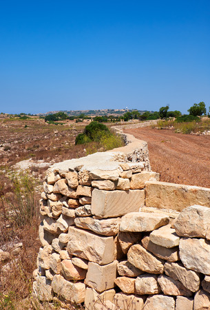 The stone fences stretch across the fields of scorched earth of Qrendi on Malta south coast. Stock Photo