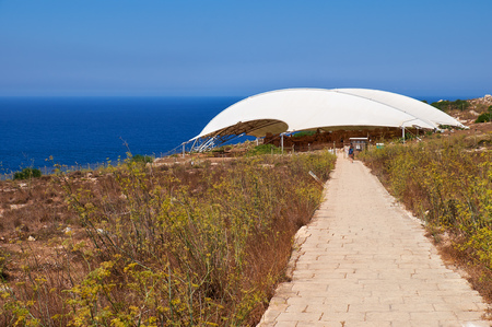 megaliths: The brick road to the megalithic temple of Mnajdra covered by protective tent. Malta Stock Photo