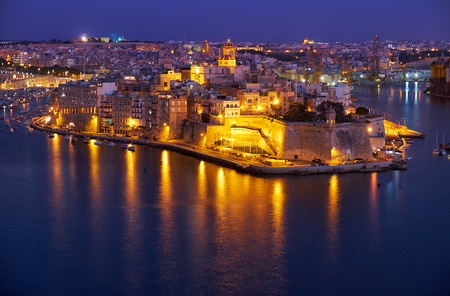 The night view in blue hour of Grand harbor and Senglea peninsula from Valletta, Malta Stock Photo