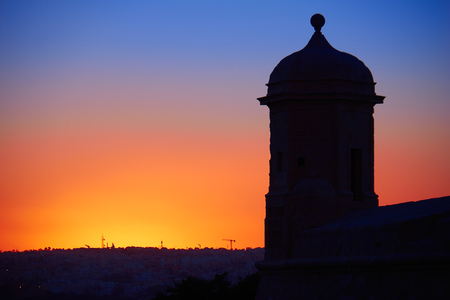 Night shot of The Guard tower on the tip of the St Peter and Paul counterguard against backlight of the sunset. Valletta, Malta Stock Photo
