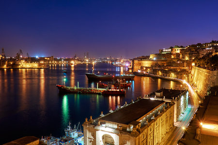 citadel: The night view of Grand Harbour with the cargo ships moored near St. Barbara Bastion from the Lower Barrakka Gardens, Valletta.