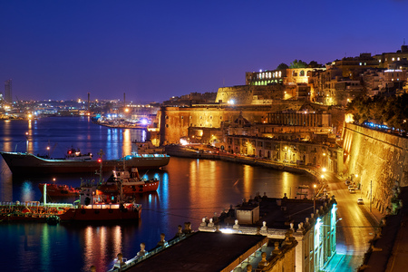 The night view of Grand Harbour with the cargo ships moored near St. Barbara Bastion from the Lower Barrakka Gardens, Valletta.