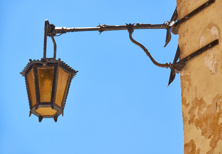 weather beaten: An old style metal street lamp hanging on the wall of a residential house in Mdina. Malta
