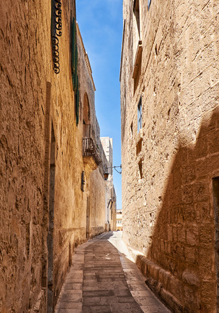narrow street: In the surroundings of limestone walls. The narrow medieval stone paved street of Mdina, the old capital of Malta. Stock Photo