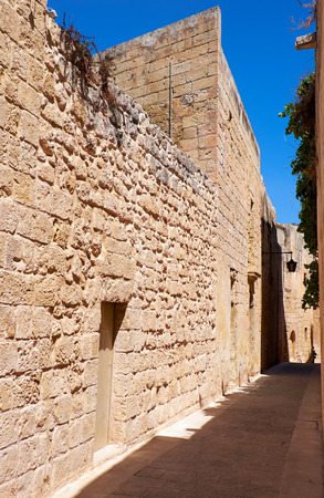 bowery: In the surroundings of limestone walls. The narrow medieval stone paved street of Mdina, the old capital of Malta. Stock Photo