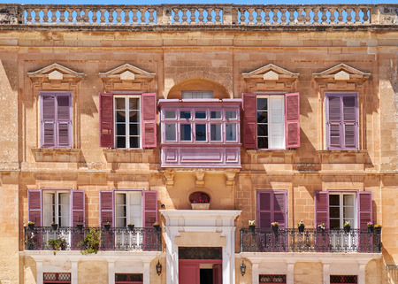 residential houses: View of one of the residential houses in Mdina with traditional Maltese style open balconies and red shutters, Malta.