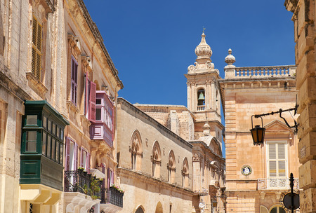 residental: A view of old Mdina street with a residental houses with a traditional Maltese style multicolored balconies and Carmelite Church Bell Tower on the background. Malta.