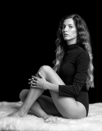 legs crossed on knee: Portrait of beautiful caucasian model posing on white furs in body on black background