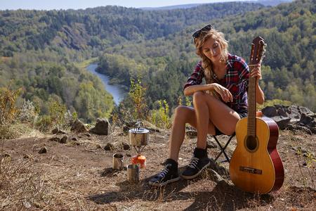 campamento: La mujer joven rubia con la guitarra turistas en el campamento en el acantilado sobre el río y el paisaje forestal Foto de archivo
