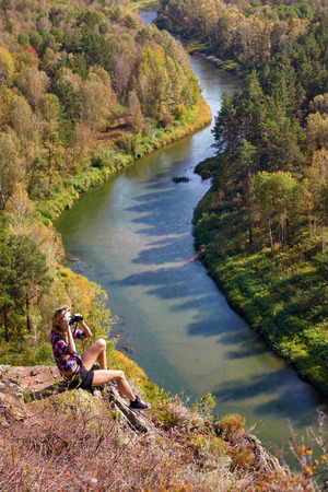 Young blonde woman tourist   on a cliff looking through binoculars on the autumn landscape with the river Berd. Russia, Siberia, Salair