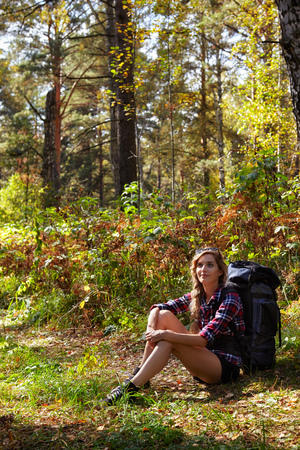 Young blonde female tourist with a backpack sitting on the sidelines of the forest path. Russia, Siberia, Salair