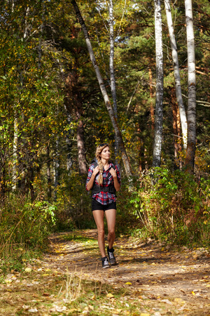 footway: Young blonde female tourist with a backpack in shirt and shorts  goes on a forest path at fall time. Russia, Siberia, Salair