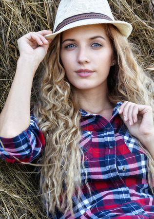 Young blonde country girl in hat sit near haystacks